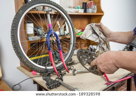 Hands of real bicycle mechanic cleaning chainring bike over workshop table in the repair process - stock photo