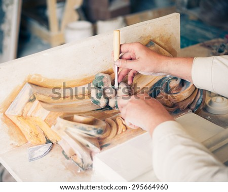 hands of restorer working with antique decor element - stock photo