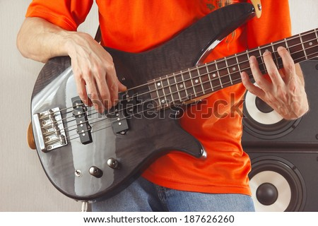 Hands of rock guitarist playing the bass guitar - stock photo