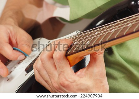 Hands of rock guitarist put guitar chords - stock photo