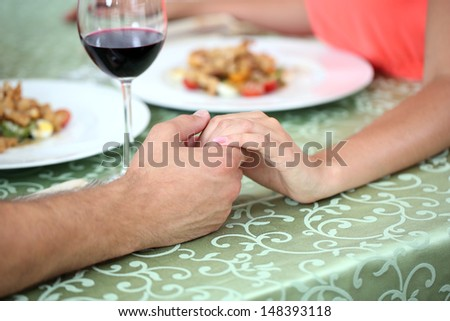 Hands of romantic couple over a restaurant table - stock photo