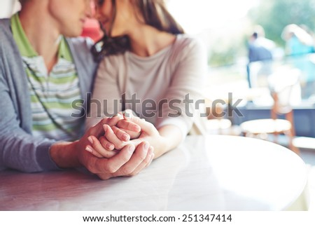 Hands of romantic couple sitting in cafe