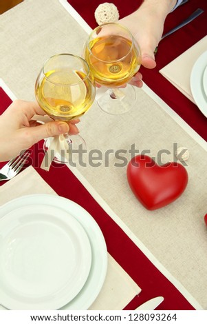 hands of romantic couple toasting their wine glasses over a restaurant table - stock photo