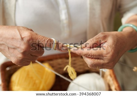 Hands of senior woman knitting a scarf