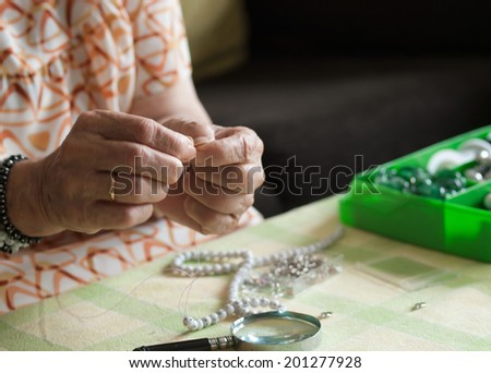 Hands of senior woman making a necklace at home