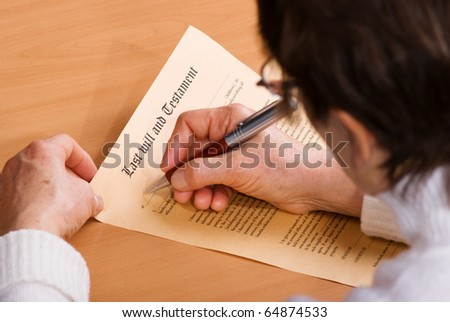Hands of senior woman signature Last Will and Testament sitting on desk - stock photo
