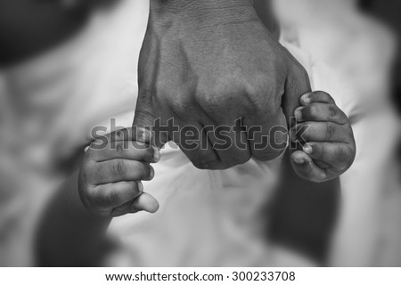 Hands of son holding his father's fingers. Black and white photography. - stock photo