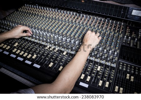 hands of sound engineer work on recording studio mixer - stock photo