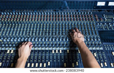 hands of sound engineer work on recording studio mixer, mixing board - stock photo