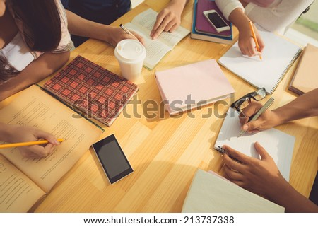 Hands of students doing homework together, view from above - stock photo