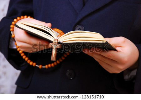 Hands of the boy going to the First Holy Communion holding prayer book and a rosary - stock photo