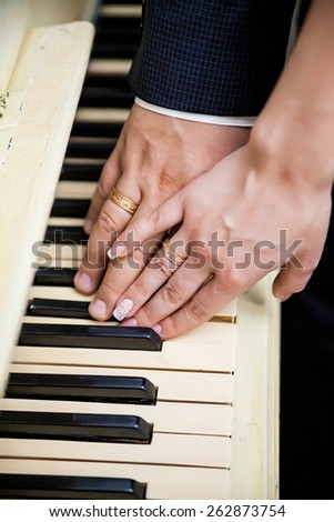 hands of the bride and groom in a wedding ring on the keys of an vintage piano - stock photo