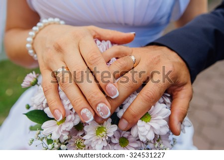 Hands of the bride and groom on the wedding bouquet