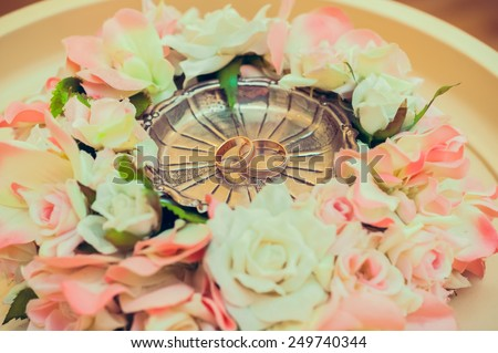 Hands of the bride and groom with rings on bouquet of roses yellow - stock photo