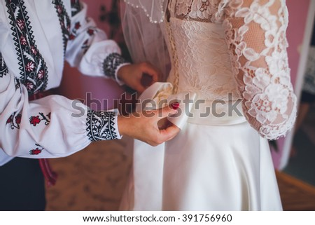 hands of the bride and her mother - stock photo