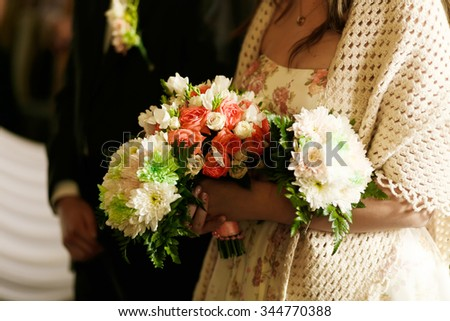 Hands of the bride with a bouquet of flowers. Wedding bouquet, floral composition. Keep flowers in hands. Wedding ceremony.  - stock photo