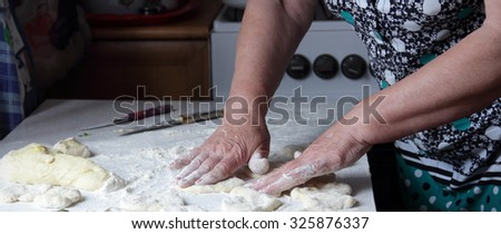 Hands of the elderly woman knead dough for pies