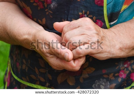 Hands of the elderly woman. The grandmother behaves by a hand.