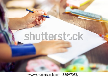Hands of the female children who keep colorful crayons on clear a white sheet of paper, in warm summer day in the park on the wooden table. Girl start to plan painting on white background. - stock photo