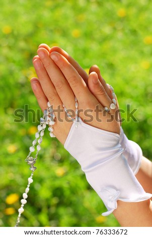 hands of the girl going to the First Holy Communion set in amen and praying with rosary against green grass background - stock photo