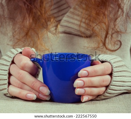 Hands of the girl with a cup of tea - stock photo