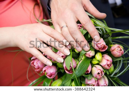 Hands of the groom and bride with rings and bridal bouquet of flowers