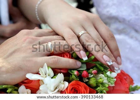 hands of the groom and the bride on background of wedding bouquet