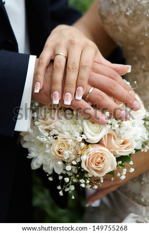 Hands of the groom and the bride on wedding flowers - stock photo