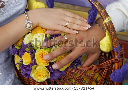 Hands of the groom and the bride on yellow purple wedding flowers - stock photo