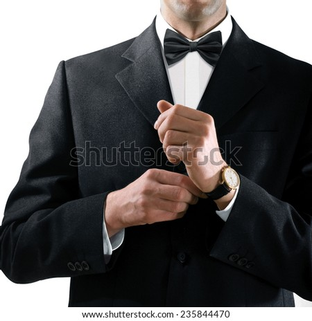 hands of the man who in a black tuxedo puts on his watch - stock photo