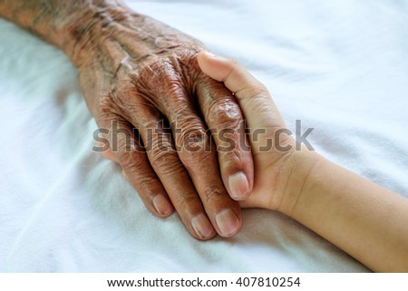 Hands of the old man and a child's hand on a white bed in a hospital.