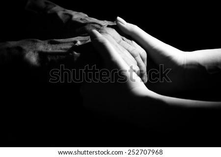 Hands of the old man and a young woman. Black and white. in low key - stock photo