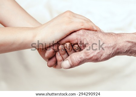 Hands of the old man and a young woman. close up. toning - stock photo