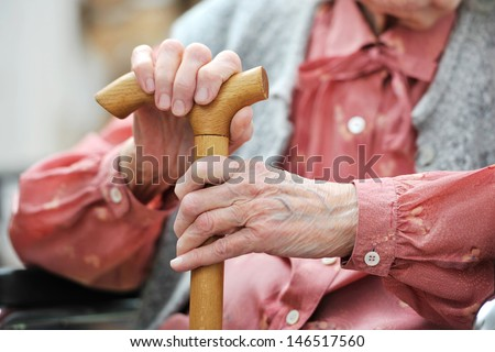 Hands of the old woman with a cane - stock photo