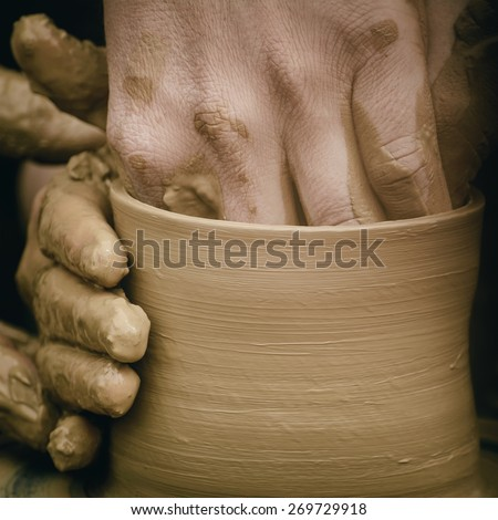 Hands of the Potter in Process of Creation of a Bowl - stock photo