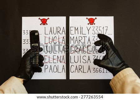 hands of the stalker wrapped in gloves black with the phone   are the sign of a threat of death for women whose names appear on the list - stock photo