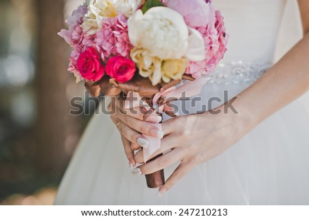 Hands of the woman hold a bunch of flowers.