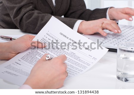 Hands of the woman signature document sitting on desk - stock photo