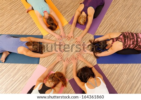 Hands of the women forming circle at Yoga class - stock photo
