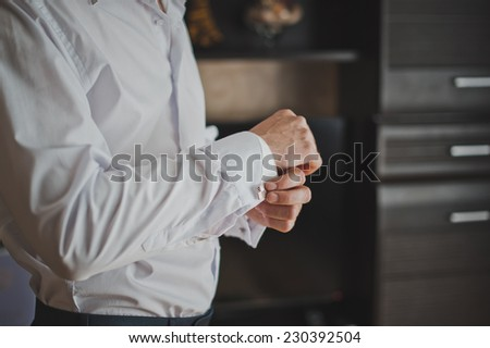 Hands of the young man clasping cuff links on shirt cuffs. - stock photo