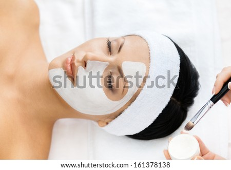 Hands of therapist apply cream to half-face of woman with closed eyes. Concept of care and youth - stock photo