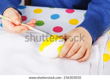 Hands of toddler boy painting colorful eggs for Easter hunt, traditional action in Germany for Eastern holiday, indoors - stock photo