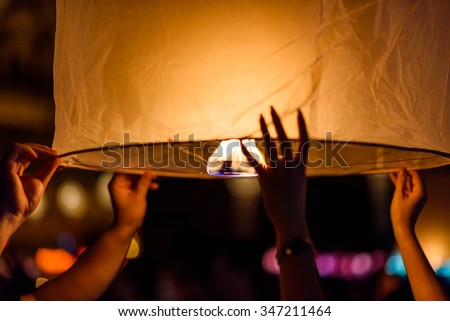 Hands of  tourist launching sky lantern to the sky , Loy Krathong festival - stock photo