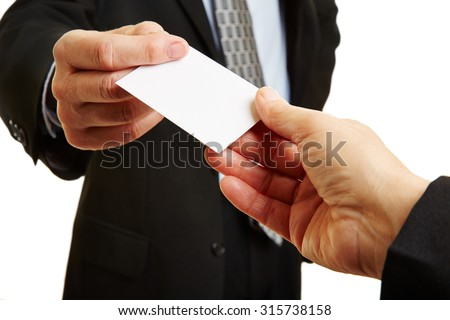 Hands of two businesspeople giving and taking an empty business card - stock photo
