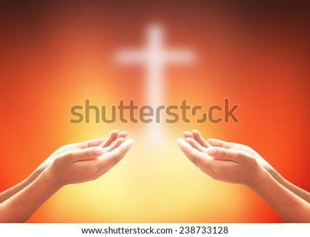 Hands of two men praying over blurred the cross on a sunset. - stock photo