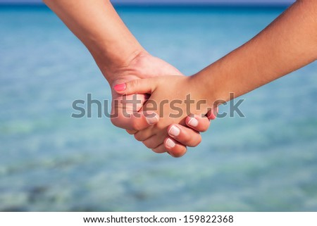 Hands of two people close up. They are standing near the sea and holding each other - stock photo