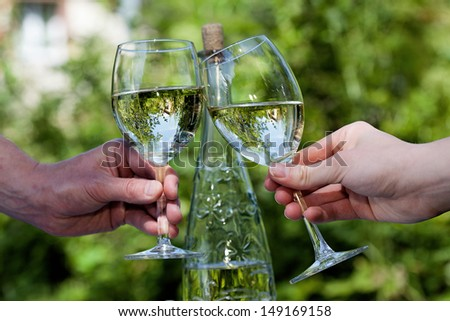 Hands of two people holding glasses with wine - stock photo