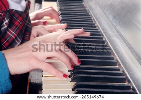 Hands of two people playing the piano. Closeup women and little girl hands - stock photo