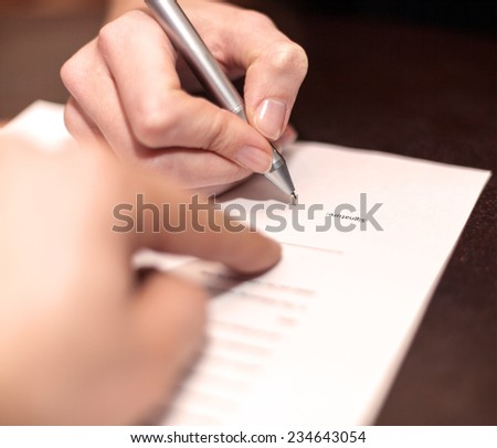 Hands of two people signed the document. - stock photo