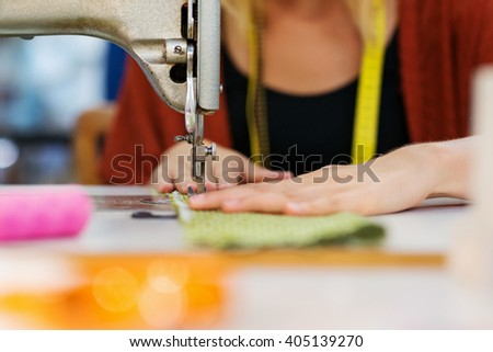 Hands of unrecognizable tailor woman working with sewing machine - stock photo